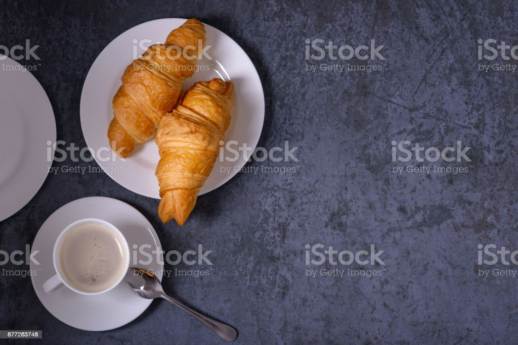 Cup of coffee and croissants on table in restaurant stock photo