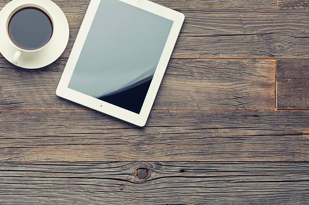 filiżanka kawy i cyfrowego tabletu na drewnianym stole. - ipad zdjęcia i obrazy z banku zdjęć