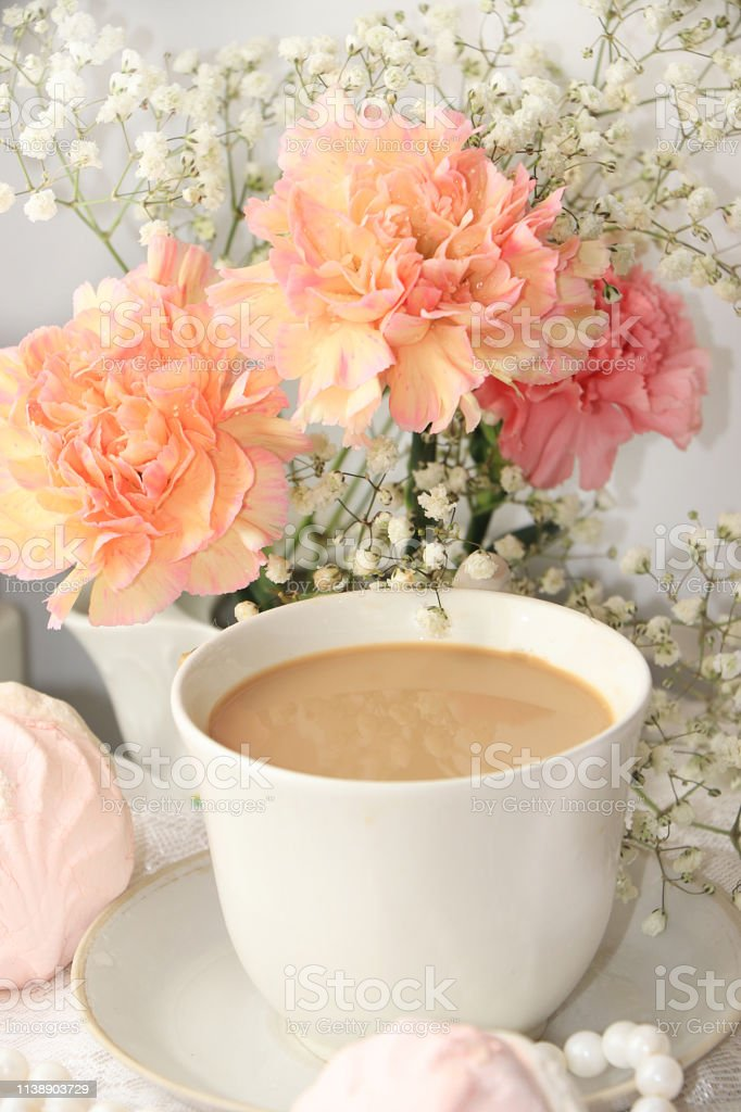 A cup of coffee and flowers on a light background, wishes of good...