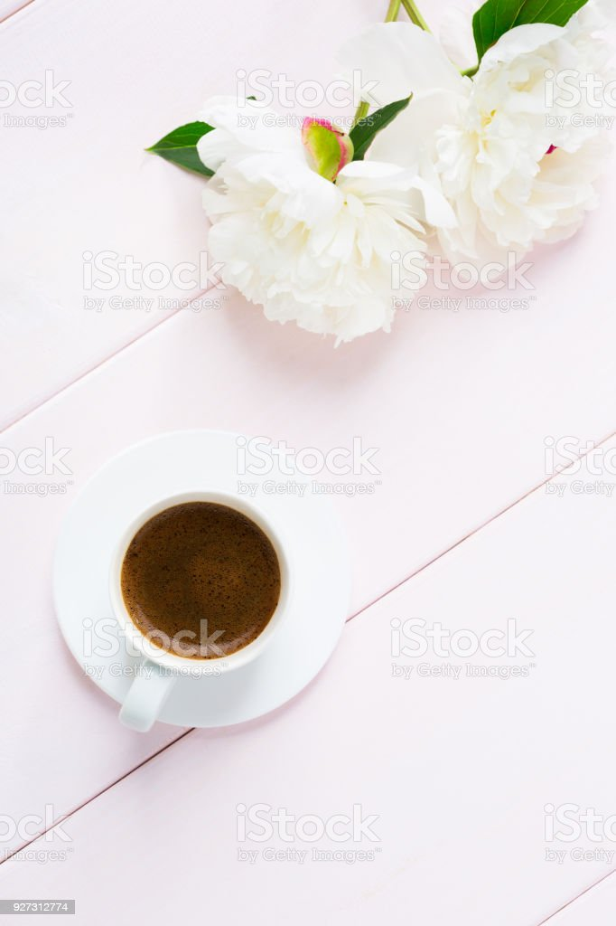 Cup of coffee and flowers on light pink wooden table.
