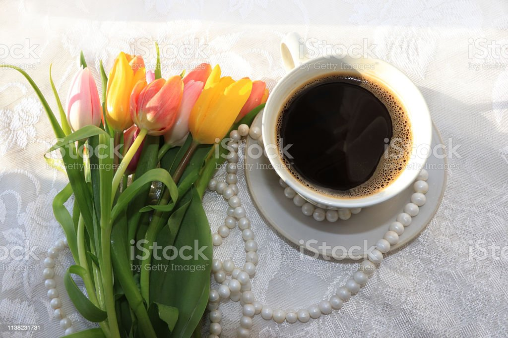 Cup of coffee and flowers in festive ribbon on pink background