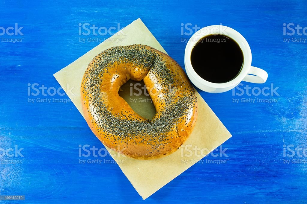 Cup of coffee and fresh bagel with poppy seeds stock photo