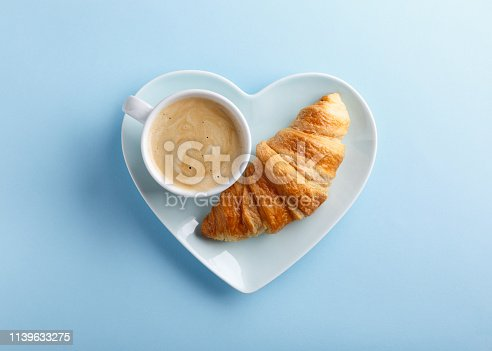 Cup of coffee and freshly baked croissants on blue background. Top view. Copy space.