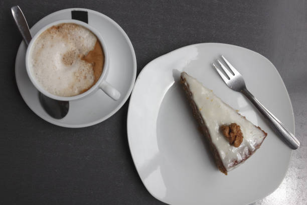 Cup of coffee and frosted carrot cake with walnut view from top stock photo
