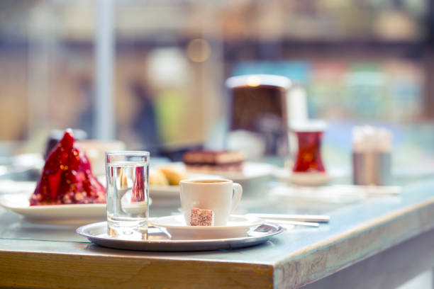 tasse kaffee und ein glas trinkwasser auf tablett - schokolade gebratene kuchen stock-fotos und bilder