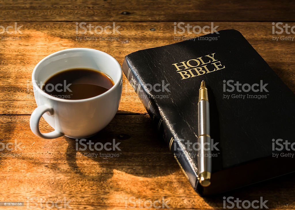 Cup of coffee and holy bible on wooden table stock photo