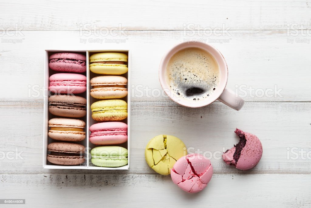 Cup of coffee and a box of colorful macarons, top view