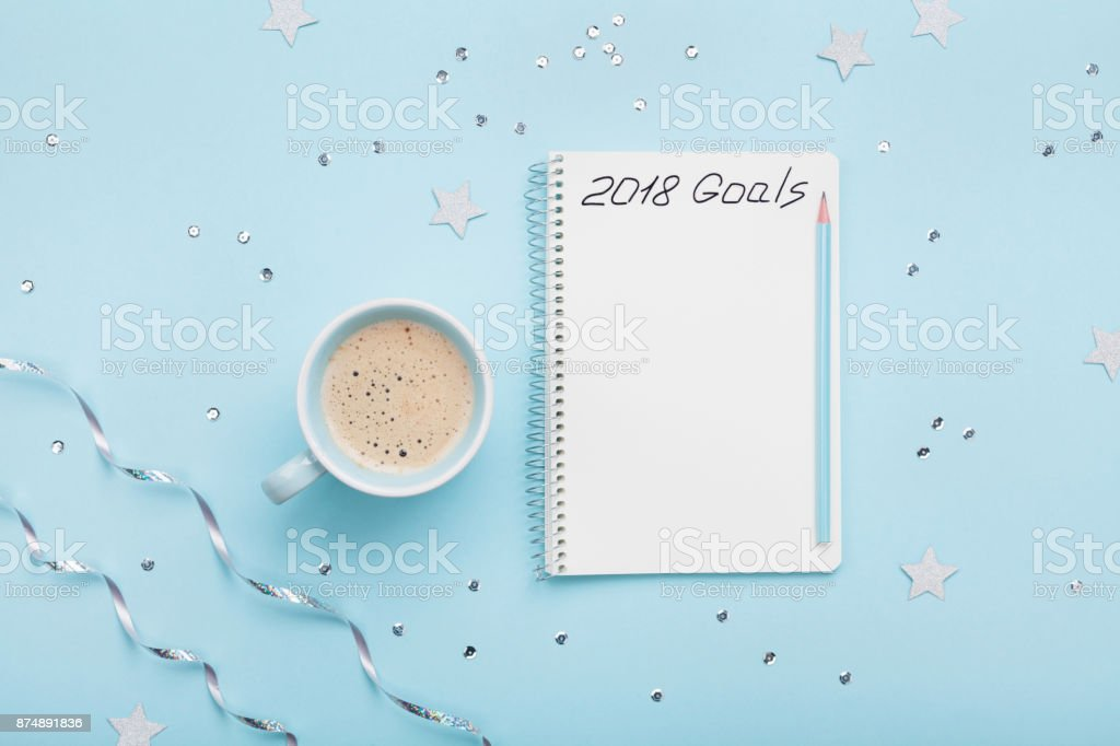 Cup of coffee and notebook with goals for 2018. Planning concept. Top view. stock photo