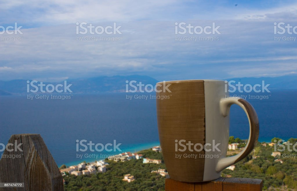 cup of coffee and ocean and beach on the background stock photo