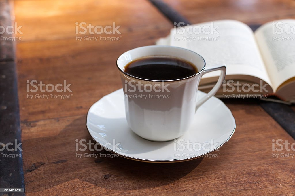 Cup of coffee and open book on a wooden table stock photo