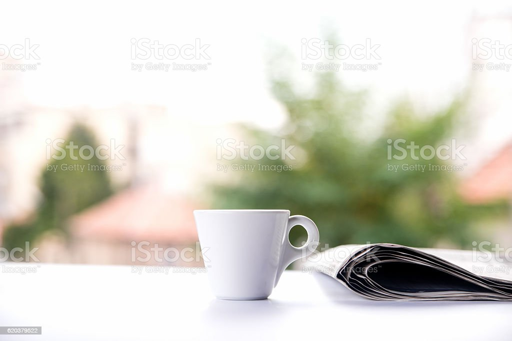 cup of coffee and the newspaper on the table outside foto de stock royalty-free