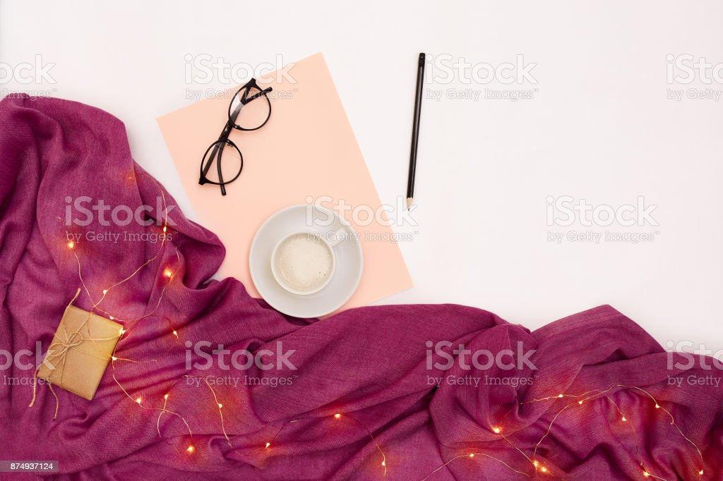 Uma xícara de café, de óculos escuros, papel rosa com metas de ano novo. Cachecol e Natal luzes no fundo branco - foto de acervo