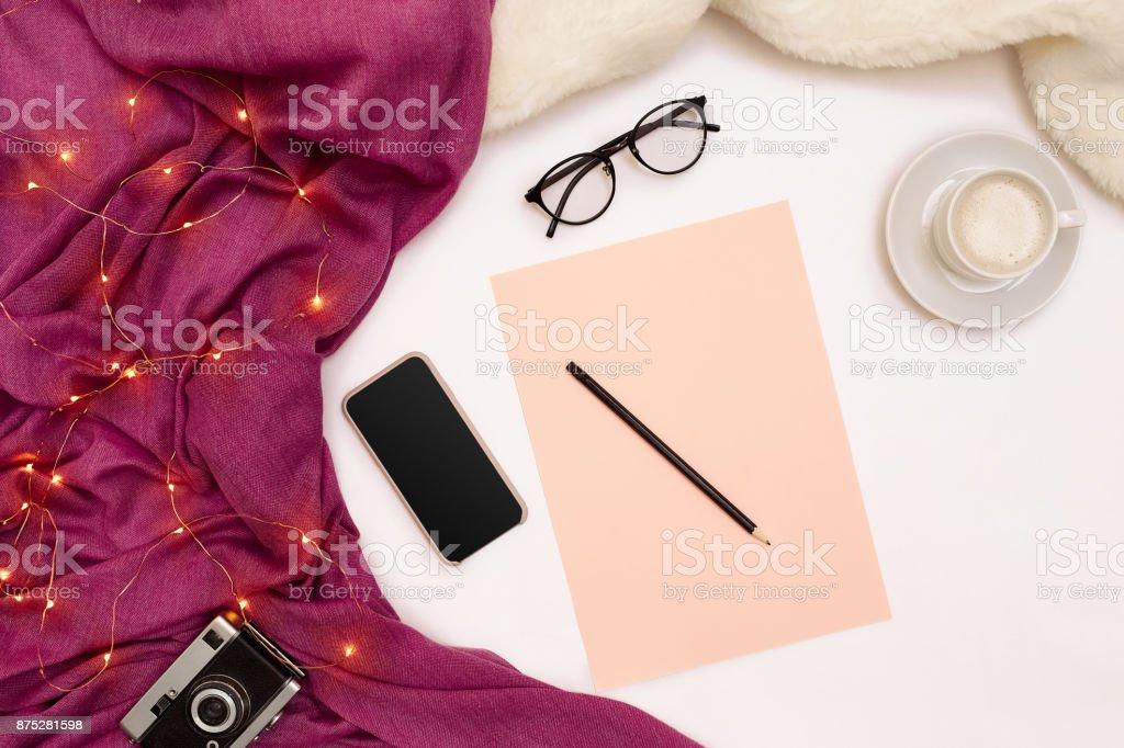 Uma xícara de café, papel inteligente, rosa preto, com metas de ano novo. Cachecol e Natal luzes no fundo branco - foto de acervo
