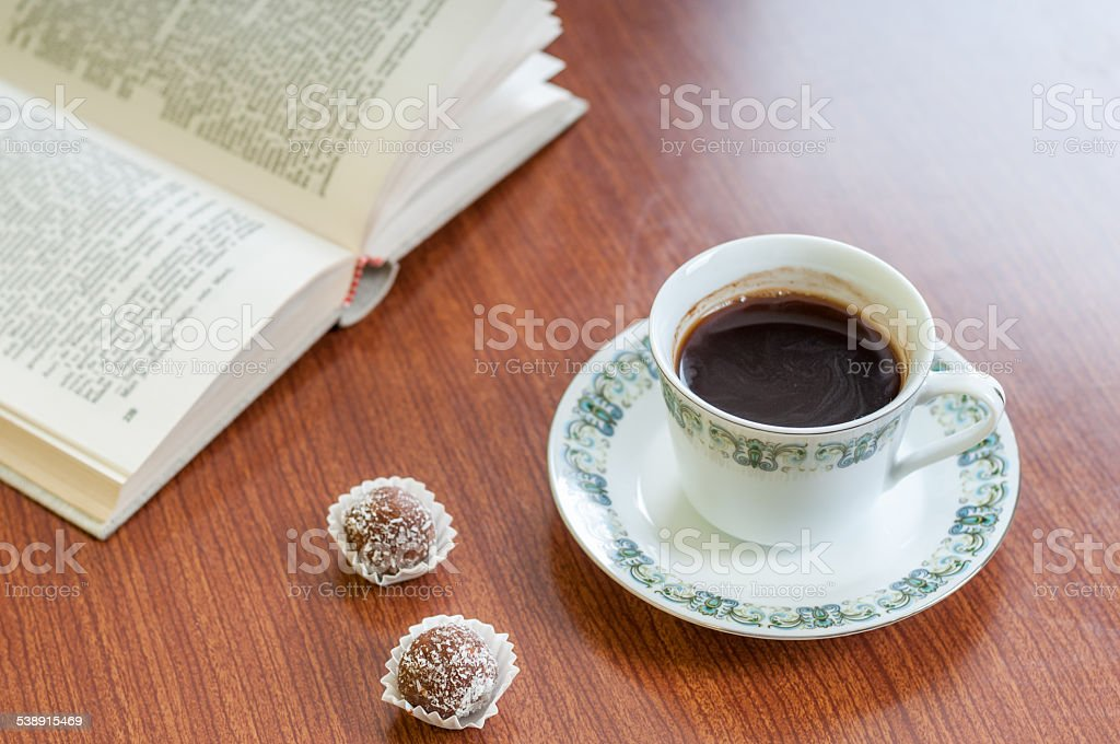 https://media.istockphoto.com/photos/cup-of-coffee-cake-and-book-picture-id538915469