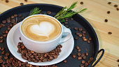 Cup of coffee, cappuccino art, coffee serving on tray, coffee beans