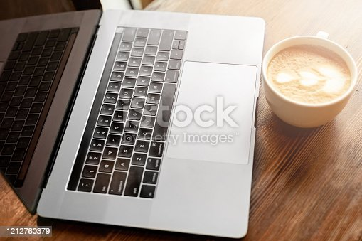 Cup of coffee cappuccino with gray laptop on wooden table. Business concept
