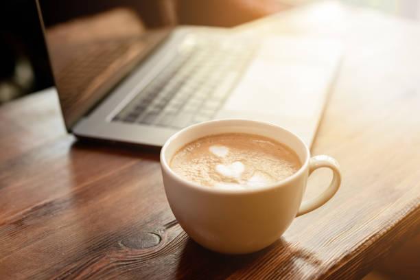 Tasse Kaffee Cappuccino mit grauem Laptop auf Holztisch. Geschäftskonzept – Foto