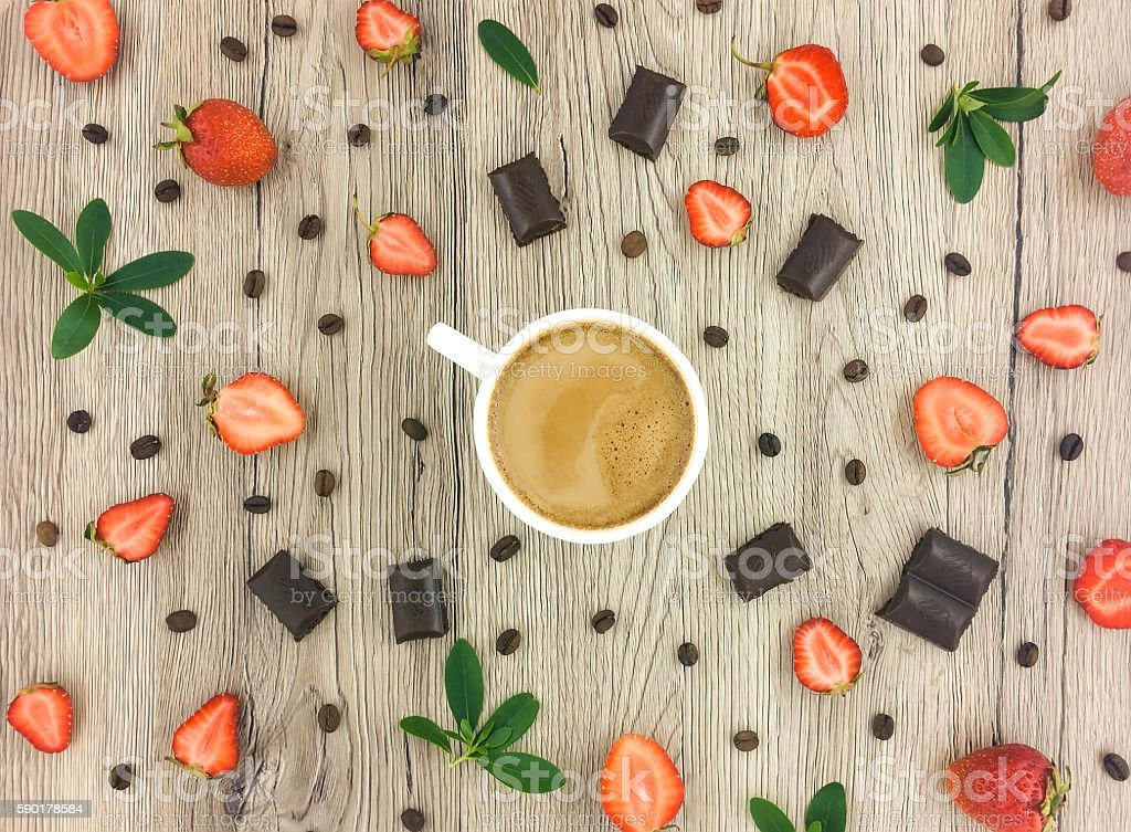 Cup of coffee, chocolate and strawberries on wood. Flat lay
