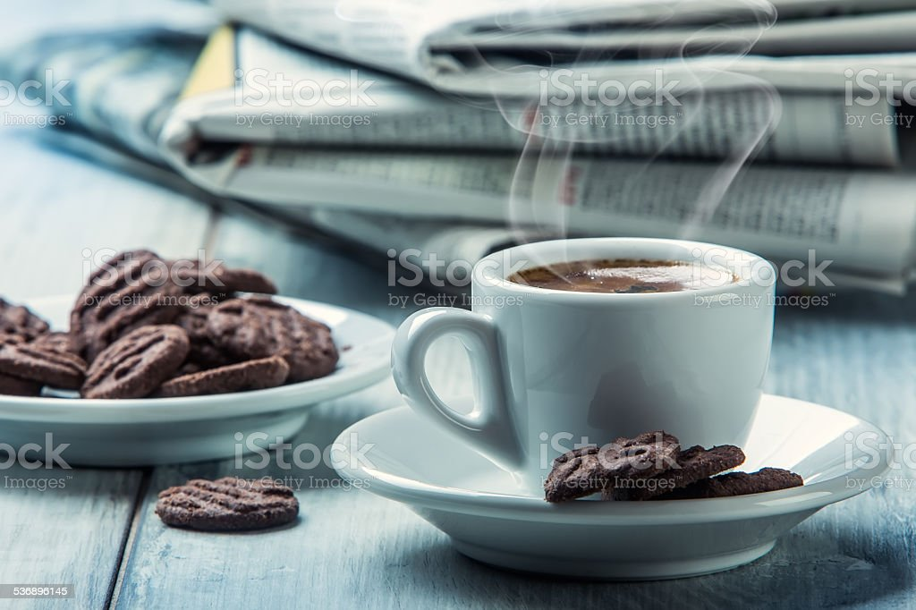 Cup of coffee , chocolate biscuits and the background newspaper. stock photo