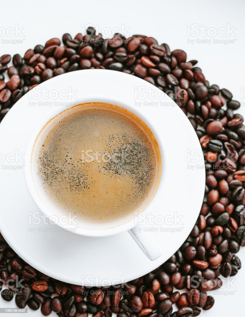 Cup of coffee close up with coffee beans on white isolated...