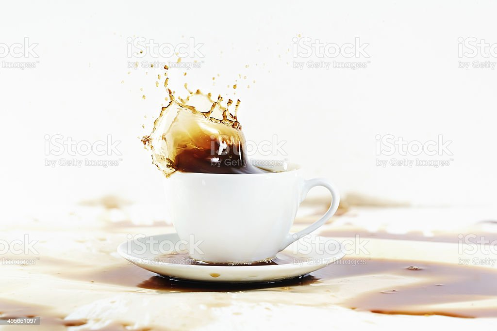 Cup of coffee creating splash. White background, coffee stains. stock photo