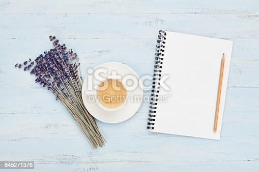 istock Cup of coffee, empty notebook and lavender flower on blue table top view. Woman working desk. Cozy breakfast. 845271376