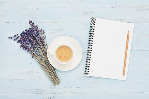 Cup of coffee, empty notebook and lavender flower on blue table top view. Woman working desk. Cozy breakfast.