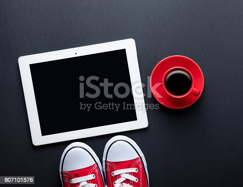 istock cup of coffee, gumshoes and tablet 807101576