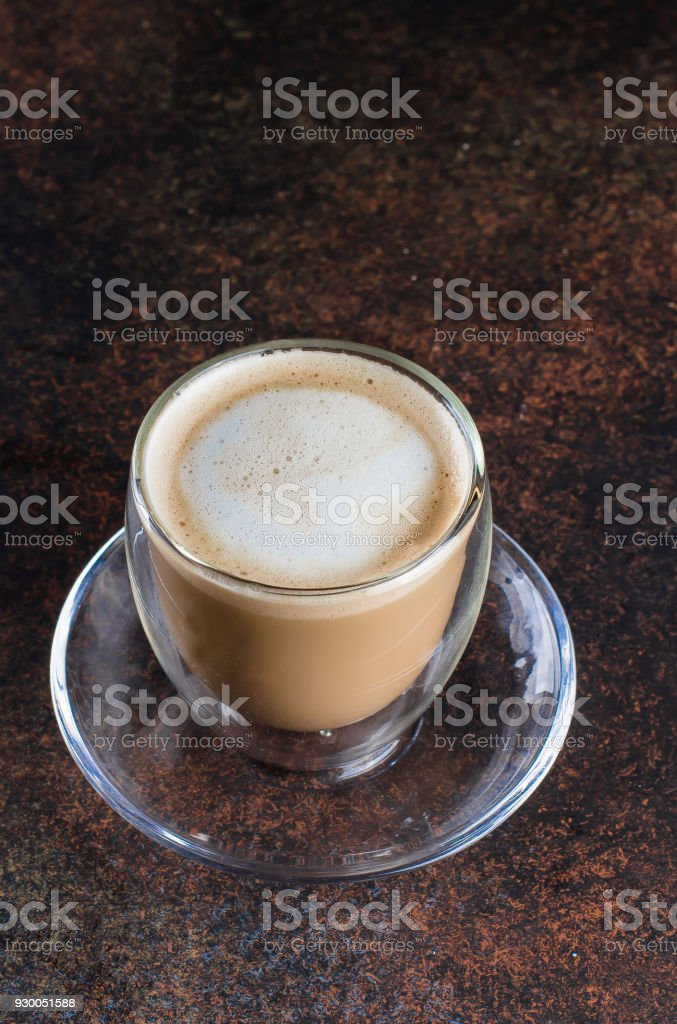 A cup of coffee in a white cup on metal dark background table. Copy...