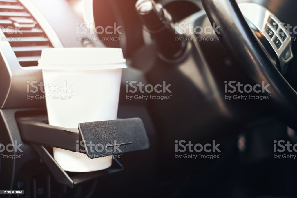 cup of coffee in cup holder in the car stock photo