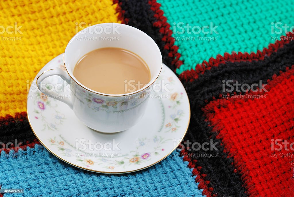 Cup of coffee in fine china dinnerware on afghan blanket stock photo