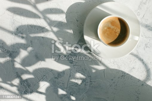 cup of coffee in the morning light, sunlight shadow, morning breakfast concept, top view, copy space