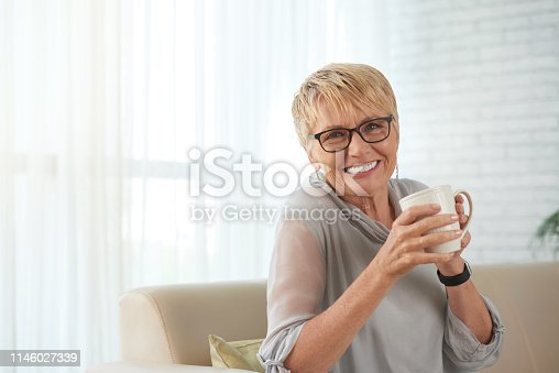 Portrait of happy mature woman in eyeglasses resting on sofa with cup of coffee and smiling at camera at home