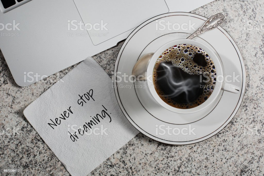 Cup of coffee, laptop and a napkin with motivation slogan stock photo