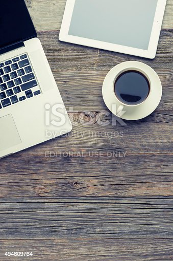 Sydney, Australia - July 27, 2015: Cup of coffee, Apple mac macbook pro laptop and Apple iPad digital tablet on wooden table. The coffee is black and you can only see part of the laptop and digital tablet. High angle view from directly above with copy space. Wood is old and distressed.