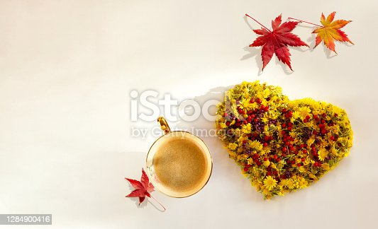 Cup of coffee, leaves of maple tree and heart-shaped flowers with copy space on isolated on white background. Autumn backgound. Top view.
