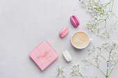 Cup of coffee, macarons, gift or present, flowers. Flat lay.