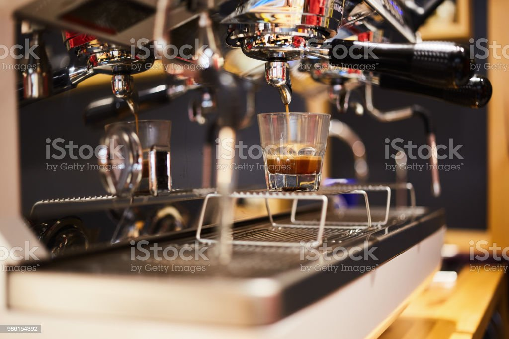 A cup of coffee machine filling coffee