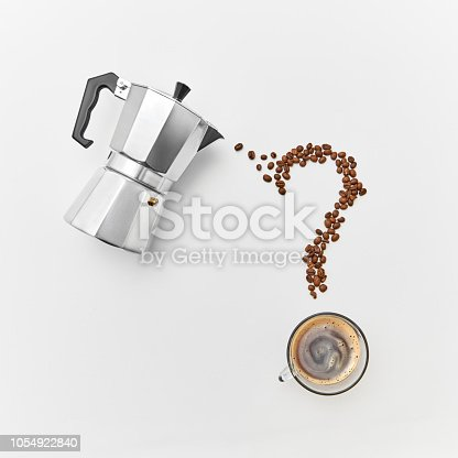 istock A cup of coffee, metal coffee maker and coffee beans in the shape of a question mark on a gray background with space for text. Flat lay 1054922840