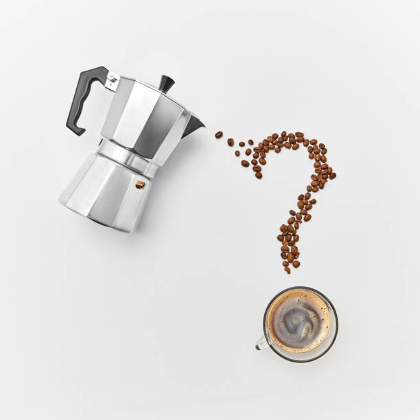 A cup of coffee, metal coffee maker and coffee beans in the shape of a question mark on a gray background with space for text. Flat lay stock photo