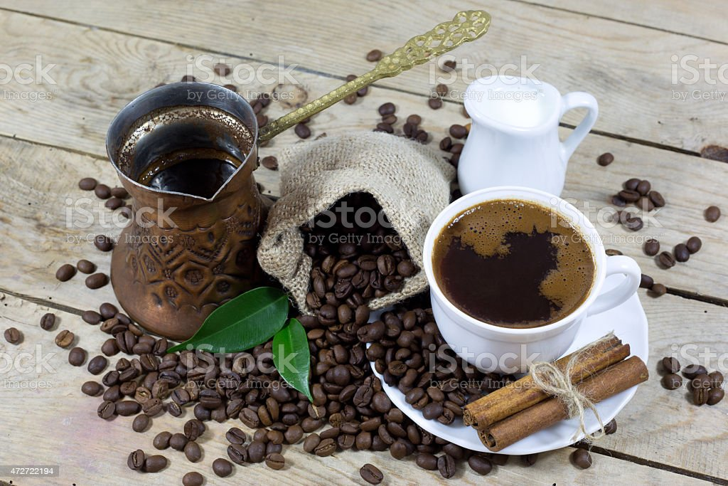 Cup of Coffee, Milk, Coffee Beans and Copper Coffee Pot stock photo