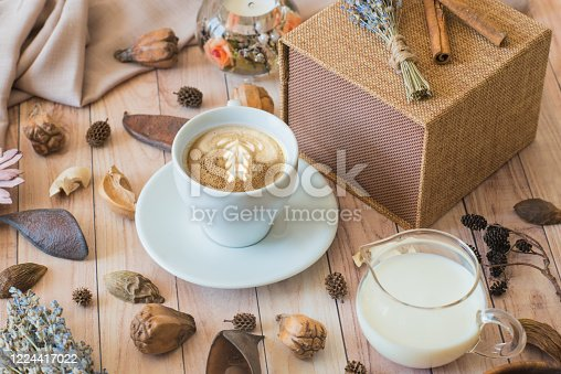1009835562 istock photo A cup of coffee, milk, gift box, and decoration on a wooden background. Cozy breakfast 1224417022