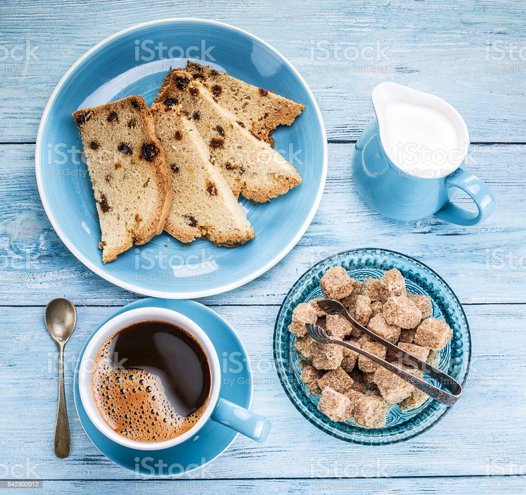 Xícara de café, Jarro de Leite, cubos de cana-de-açúcar e bolo de frutas. - foto de acervo