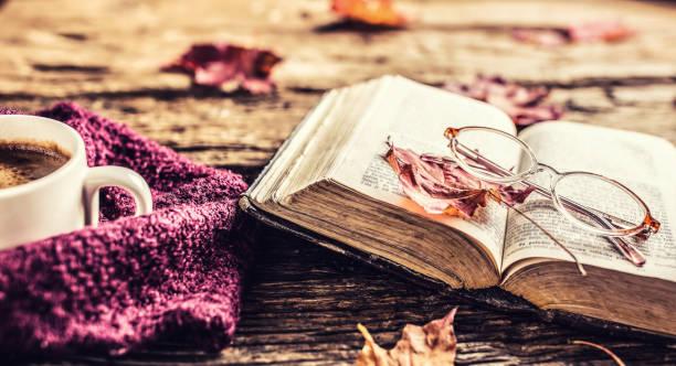 Tasse Kaffee alte Buch Gläser und Herbstlaub auf rustikalen Holztisch. – Foto