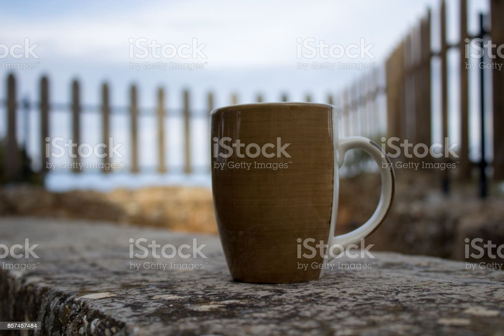 cup of coffee on a bench at a beautiful autumn mornng stock photo