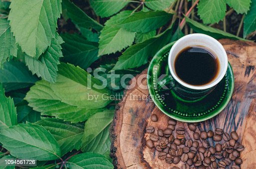 Green cup with coffee on a tree saw cut with coffee grains and green leaves.