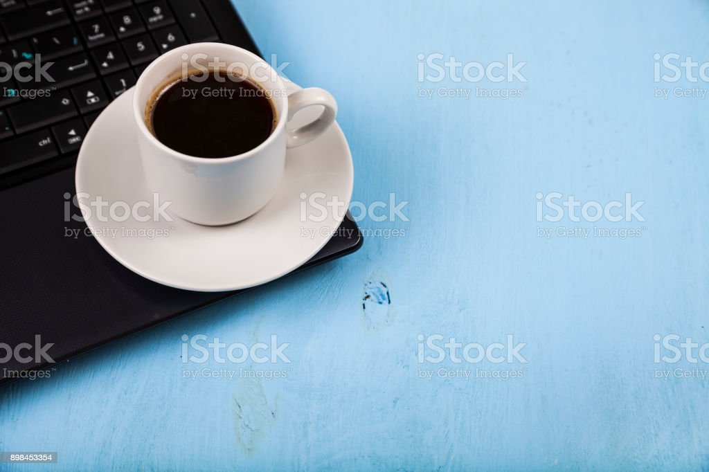 Cup of coffee on a laptop. stock photo