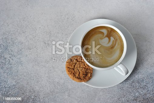A cup of coffee on a light table surface. Next to the cup on the saucer is a cookie. Free space for text. View from above.