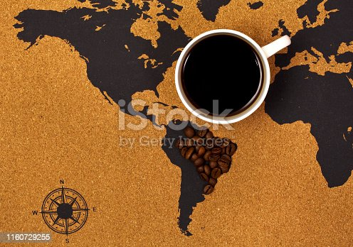 Cup of black hot coffee on a map with Brazil made of coffee beans. Top view.