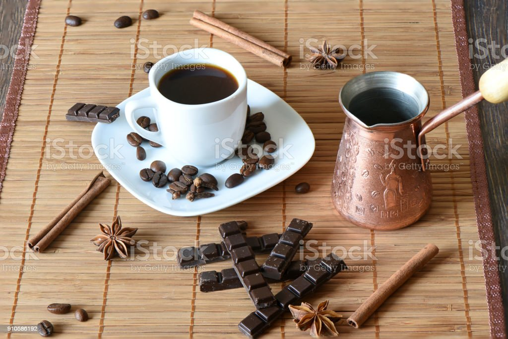 A cup of coffee on a mat, cinnamon, chocolate stock photo